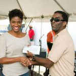 Arawak's Erwin Jones presents winning customer, Mrs. S. Lashley with her Staycation prize for two at the Almond Beach Hotel.