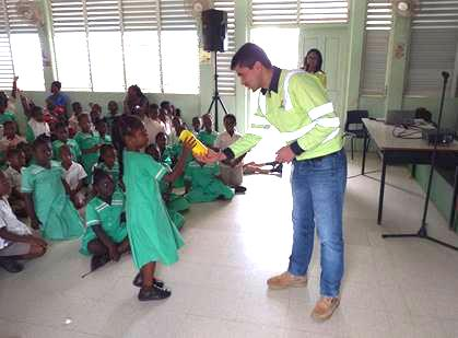 A student happily receives her token from Rafael Martinez, Procurement Manager - CAPEX Projects